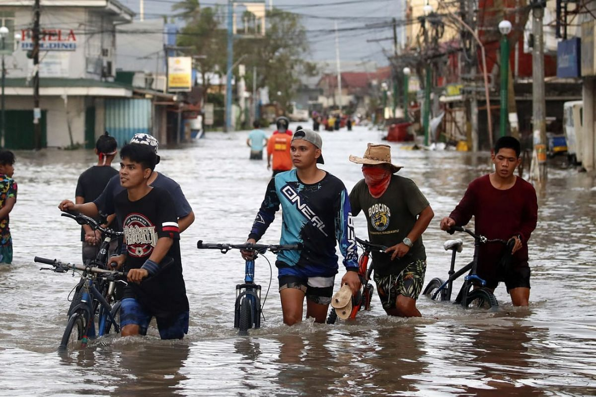 Villagers wading along a flooded road in the typhoon-hit town of Nabua, Camarines Sur, Nov 1, 2020.