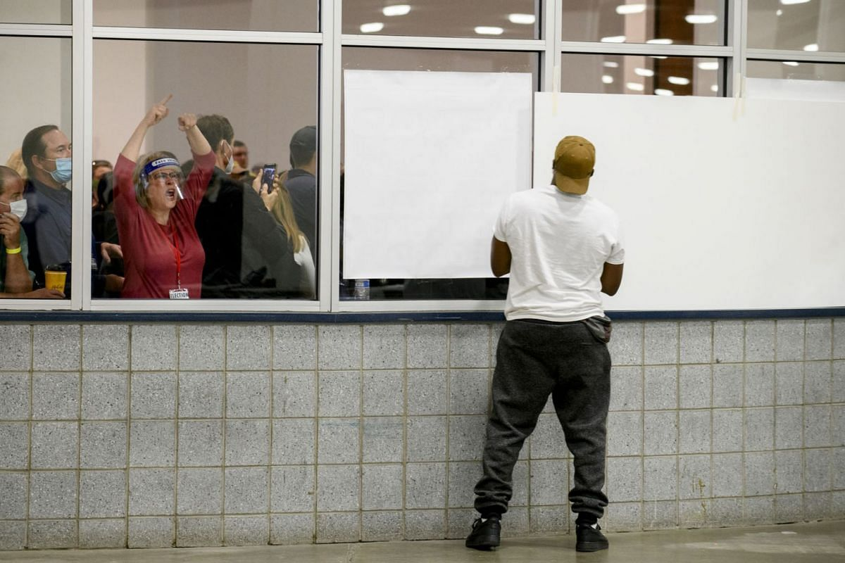 Supporters of President Donald Trump and Republican operatives bang on the glass outside a vote-counting site in Detroit, chanting  'Stop the count', Nov. 4, 2020.