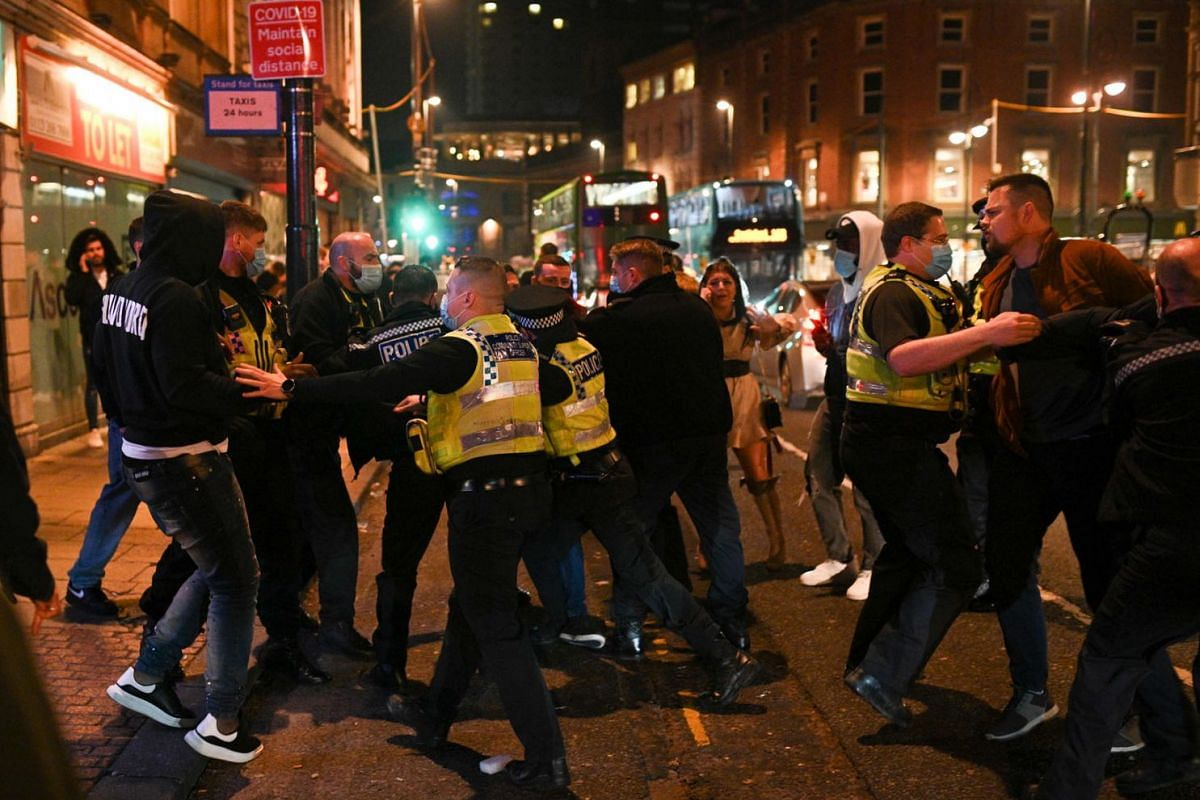 Police officers scuffle with revellers in the street after pub closing time in Leeds, northern England on November 4, 2020, on the eve of a second novel coronavirus COVID-19 lockdown in an effort to combat soaring infections.