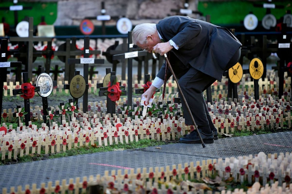 A man places a Cross of Remembrance in the Field of Remembrance at Westminster Abbey in central London on November 4, 2020.