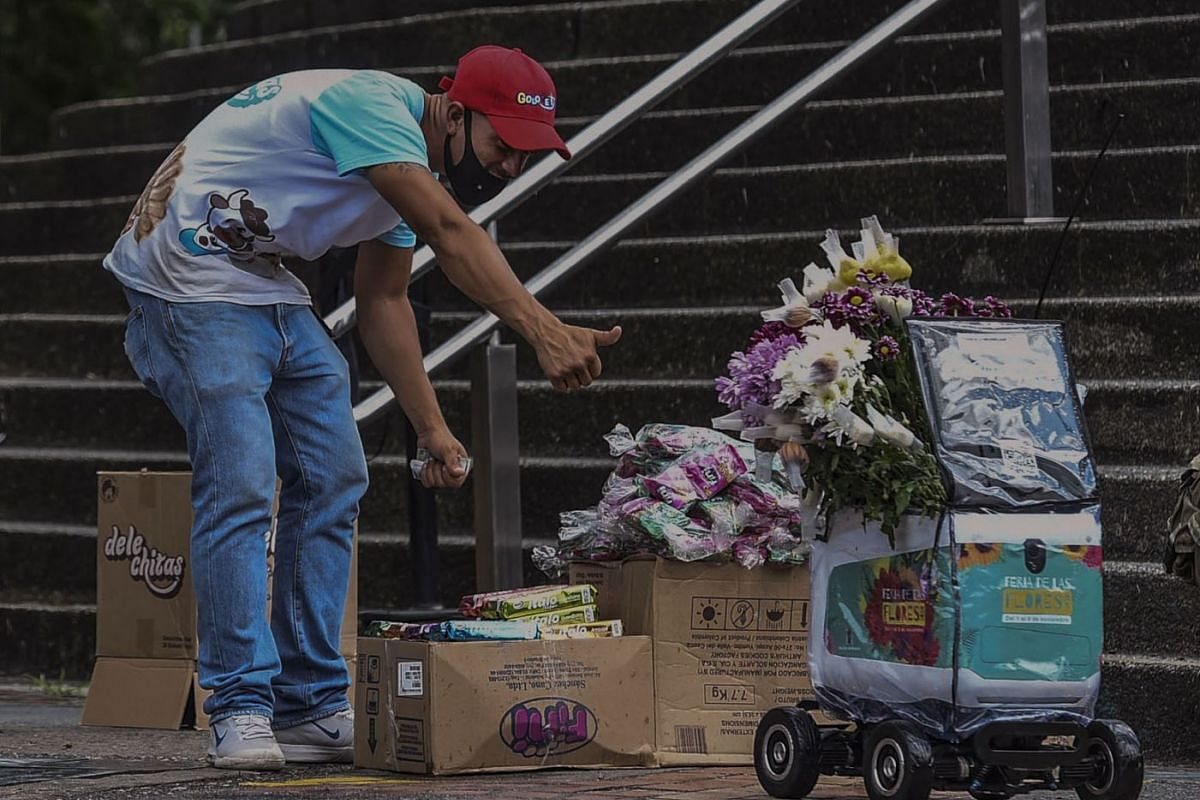 A man gives a thumbs up to a delivery robot used to promote Medellin's Flower Festival by giving flowers for free in Medellin, Colombia on November 4, 2020.