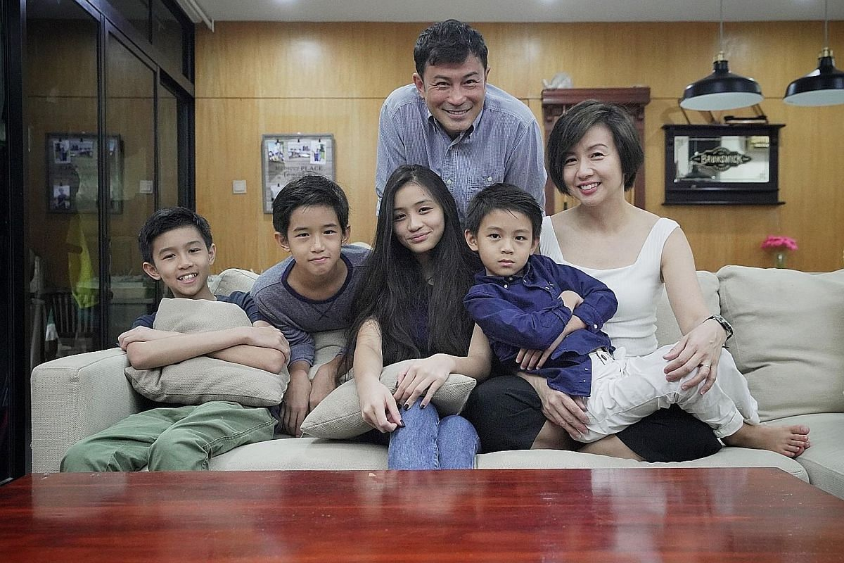 Evelyn Tan and Darren Lim with their children (above, from left), Jairus, 13, Way, 11, Kristen, 15, and Elliott, seven. The family now live in a condominium unit in Upper Changi. Darren Lim's 500 sq ft, three-room Lagoon 400S2 catamaran (left) is amo