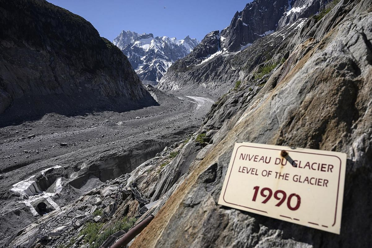 A 2019 photo of a board indicating the level of the Mer de Glace glacier in France in 1990. The glacier has shrunk drastically over the past three decades. According to a New Scientist report in 2019, visitors exiting a nearby train station could des