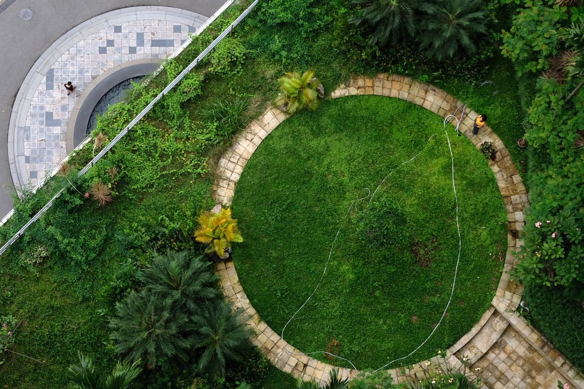 #UNENDING: An overhead view of an outdoor garden at Fairmont Singapore last Wednesday. The circular path is a reminder of the unending fight against the coronavirus. Covid-19 has become a serious economic, social and political problem that will not g