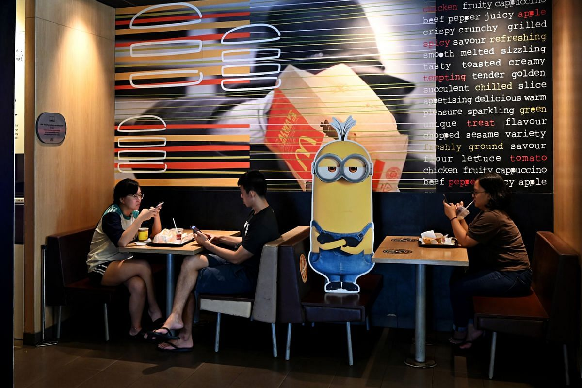 #SOCIAL DISTANCING: Diners having their breakfast – next to a cardboard cut-out of a character from the Minions 2 movie to promote safe distancing – at a McDonald's in Punggol on Sept 7. As social distancing becomes a way of life, people have b