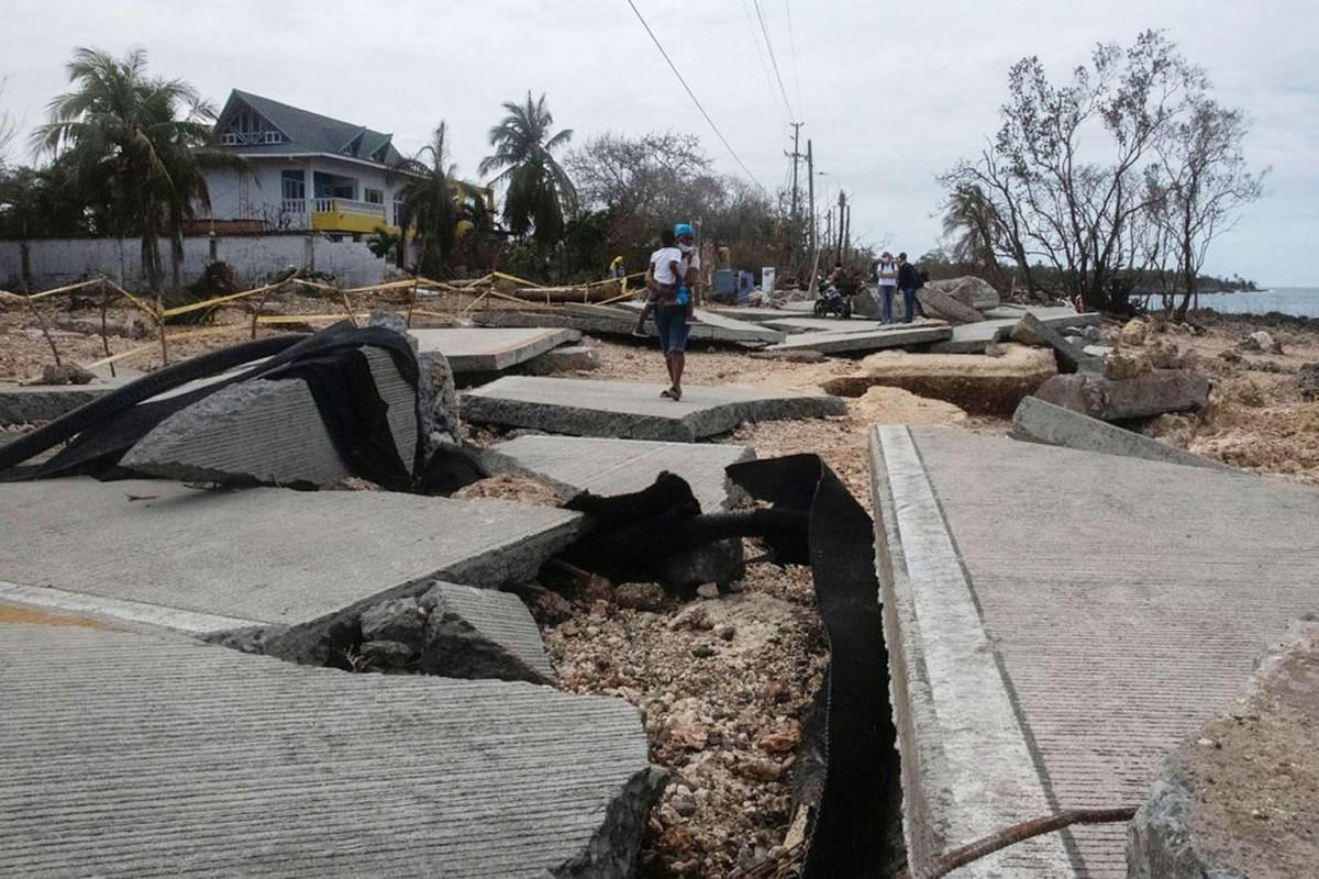 People walk on a destroyed street in San Andres, Colombia, Nov 18, 2020. Hurricane Iota left at least two dead, one missing, thousands of victims and several injured.