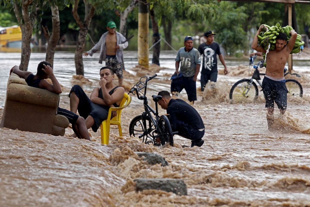 A man carries bananas as he crosses a flooded street in El Progreso, department of Yoro, Honduras on November 18, 2020, after the passage of Hurricane Iota.