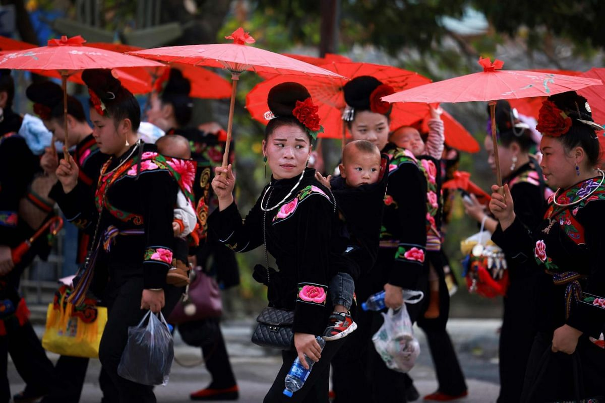 This photo taken on November 18, 2020 shows people of the Miao ethnic minority in traditional costumes parading to celebrate the Miao new year festival in Leishan county, in China's southwestern Guizhou province.