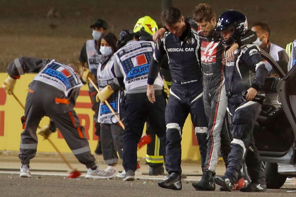 Stewards and medics attend to Haas F1's French driver Romain Grosjean after a crash at the start of the Bahrain Formula One Grand Prix at the Bahrain International Circuit in the city of Sakhir on Nov 29, 2020.