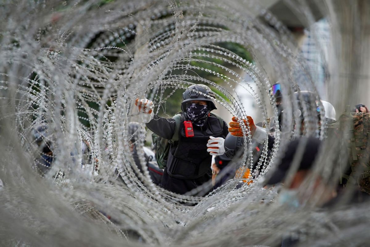 Protesters try to remove barb wires ahead of a pro-democracy rally demanding the prime minister to resign and reforms on the monarchy, in front of 11th Infantry Regiment, in Bangkok, Thailand, on Nov 29, 2020.