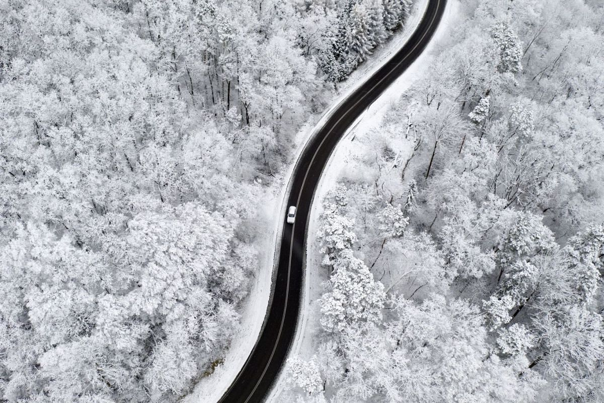 A picture take with a drone shows a provincial road through a forest with trees covered in snow near the village of Korytniki in Podkarpacie region, south-eastern Poland, on Nov 29, 2020.