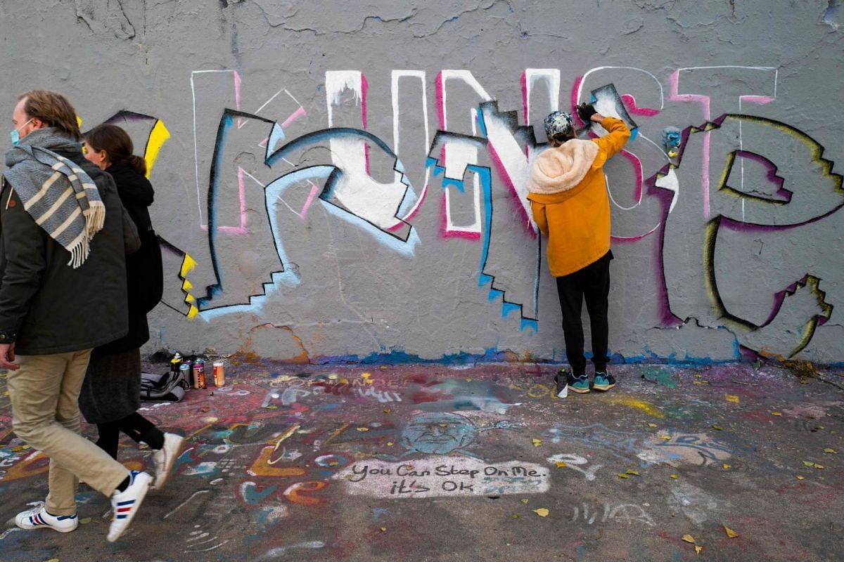 """ART FOR ART'S SAKE: A street artist painting the word """"kunst"""" (German for art)."""