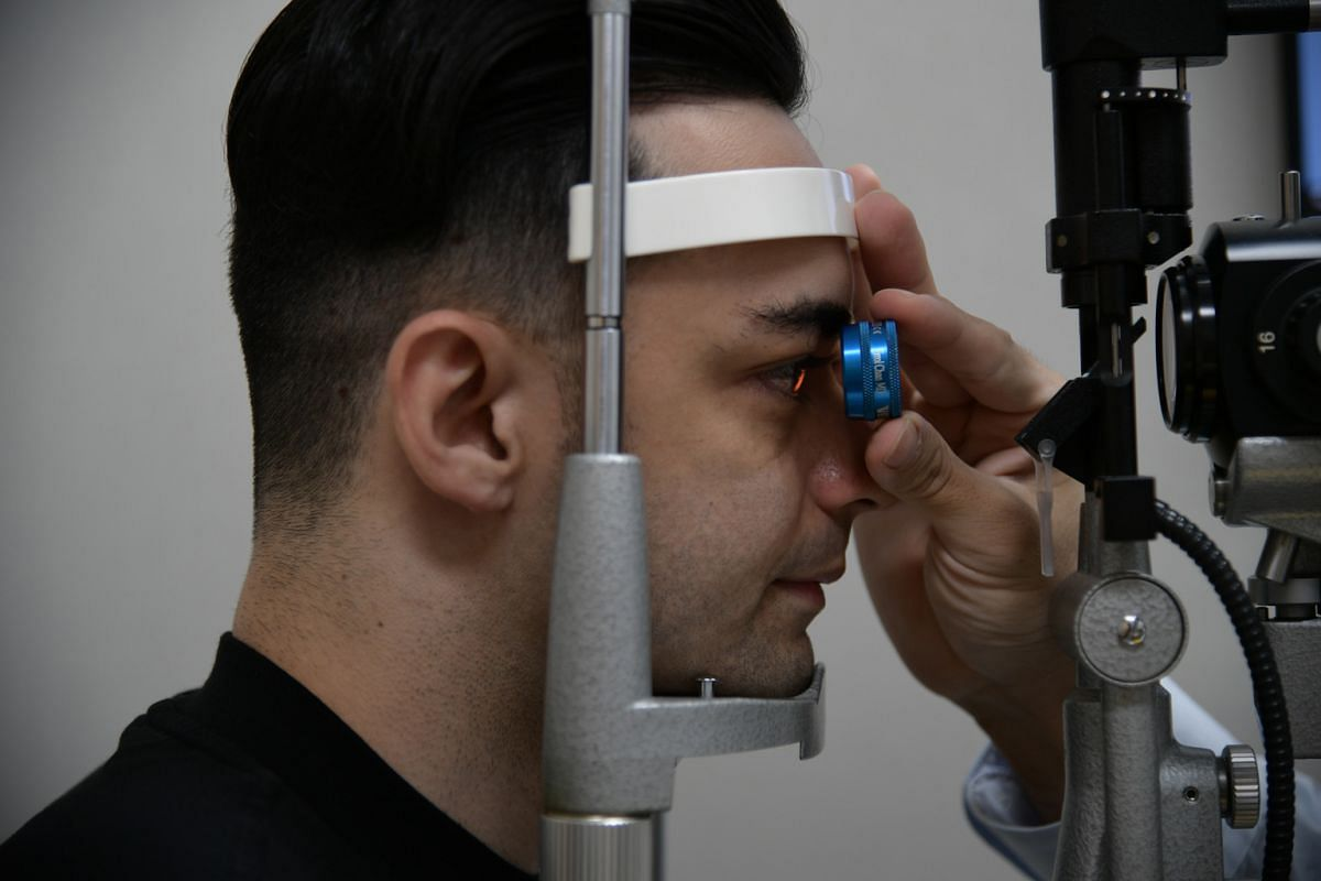Dr Errol Chan performing a slit lamp examination to detect abnormalities in the front of the eye and looking at the back of the patient's eye (above). Adults aged 20 to 39 should go for a comprehensive eye examination if they are suffering from an ey