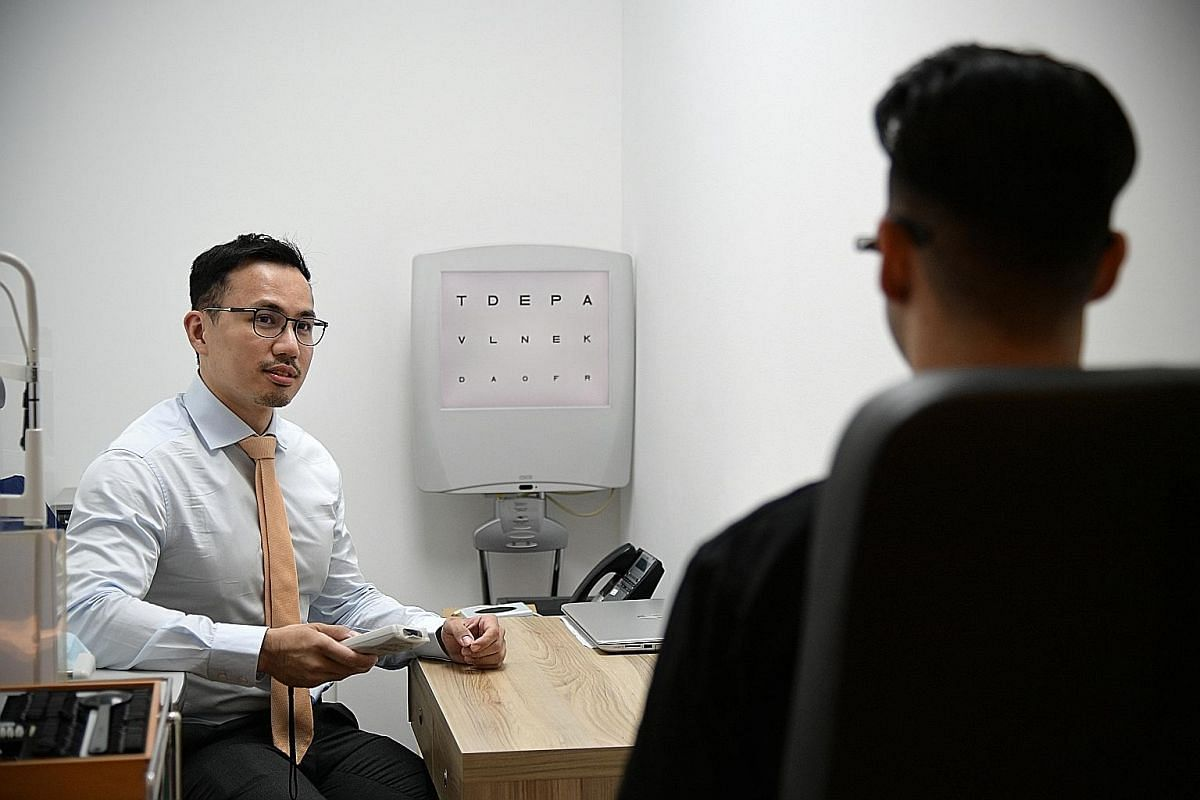 Dr Errol Chan, a consultant ophthalmologist at LSC Eye Clinic, testing how well a patient can see with the use of an eye chart.
