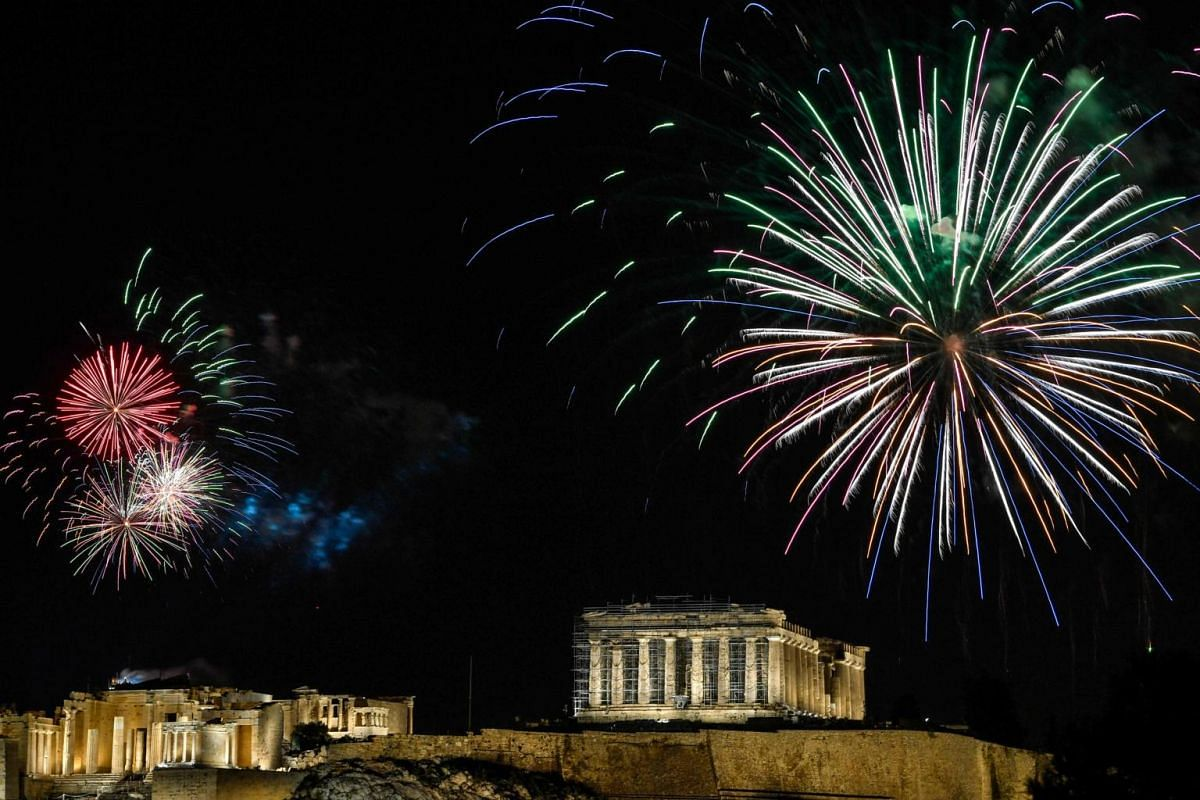 Fireworks explode over the ancient Acropolis in Athens during New Year celebrations on Dec 31, 2020.