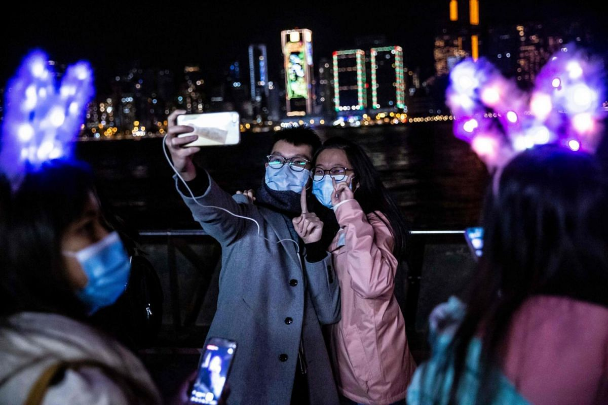 A couple take a selfie at Victoria Harbour in Hong Kong, on Dec 31, 2020. Despite the restrictions in place due to the Covid-19 pandemic, people gathered to celebrate the New Year.