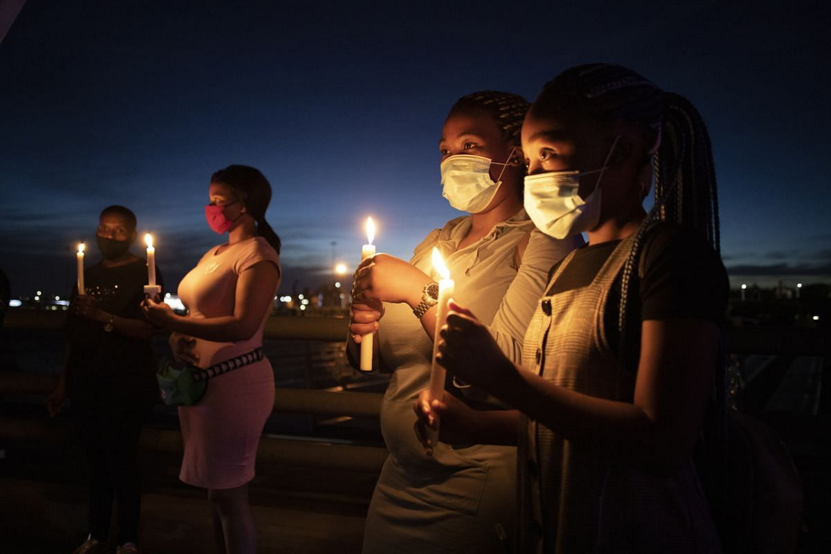 People stand with candles during a New Year's Eve memorial for victims of the coronavirus in Johannesburg on Dec 31, 2020.