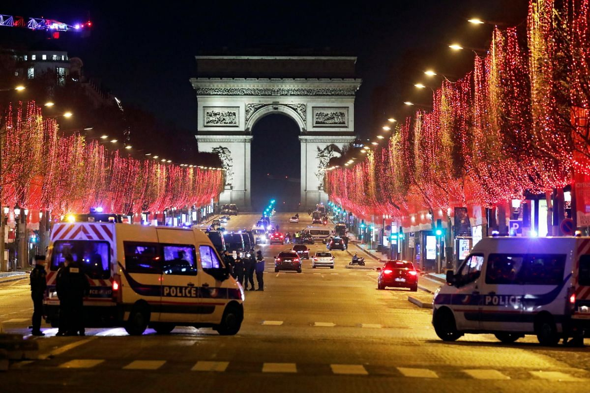 French police patrol the Champs Elysees avenue in Paris, after celebrations and gatherings have been banned amid the coronavirus pandemic, on Dec 31, 2020.