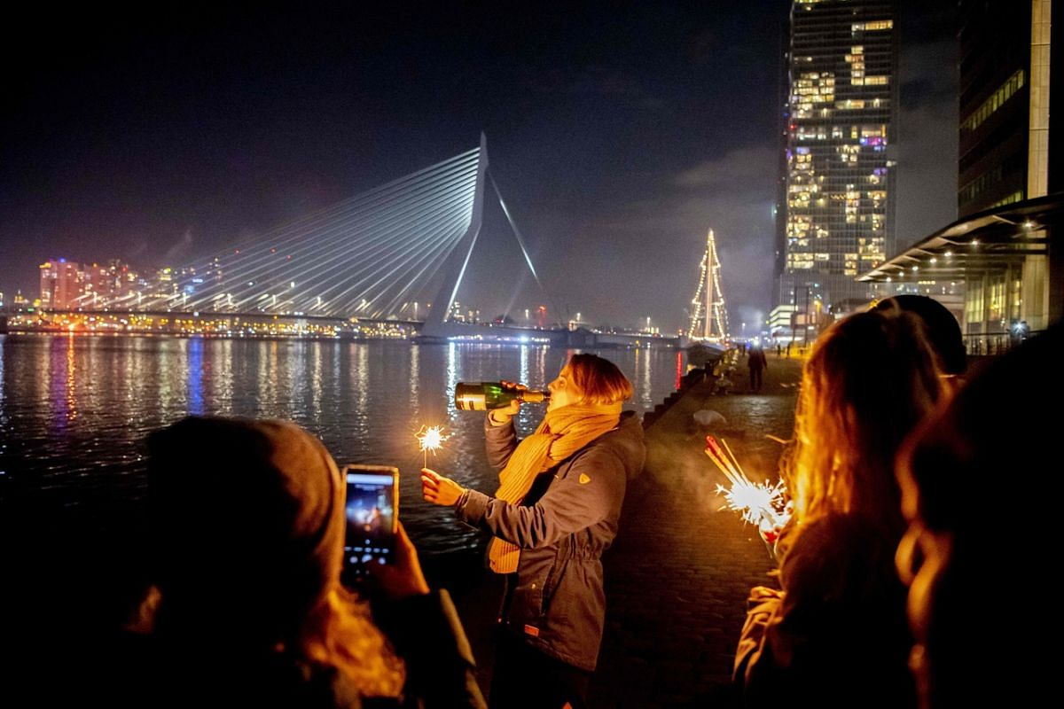 People celebrate on Rotterdam's Erasmus Bridge in the Netherlands during New Year's Eve celebrations on Dec 31, 2020.