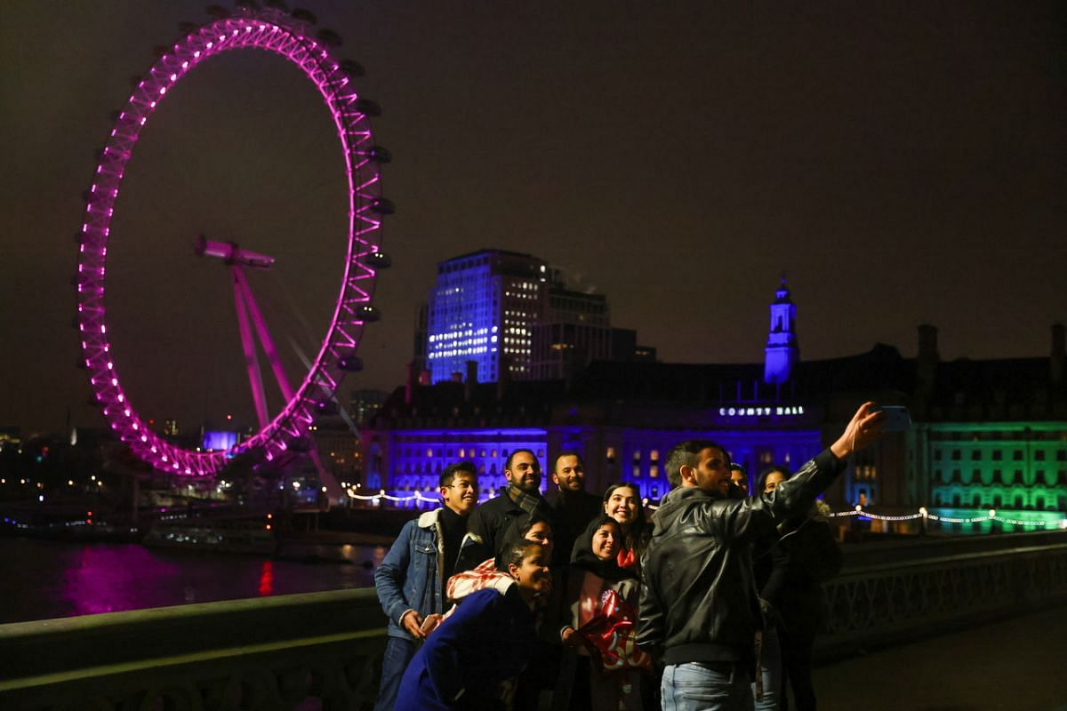 People take a selfie on Westminster Bridge during New Year's Eve celebrations in London on Dec 31, 2020.