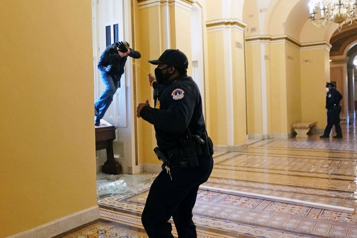 A US Capitol police officer shoots pepper spray at a protester attempting to enter the Capitol building during a joint session of Congress in Washington, DC, USA, on Jan 6, 2021.