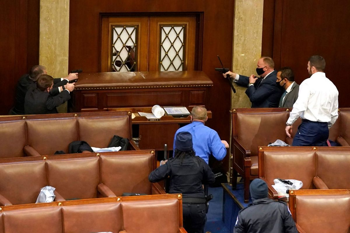 Capitol police officers point their guns at a door that was vandalised in the House Chamber during a joint session of Congress on Jan 6, 2021 in Washington, DC.