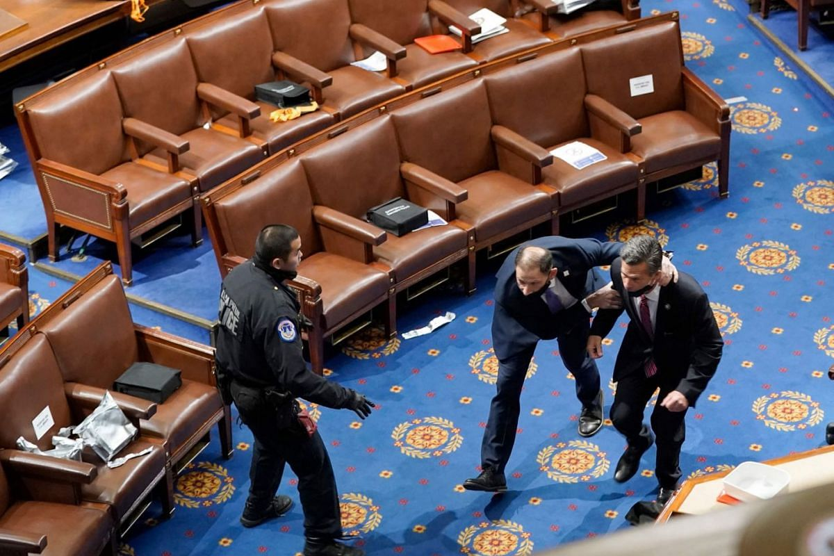 Members of congress run for cover as protesters try to enter the House Chamber during a joint session of Congress on Jan 6, 2021 in Washington, DC.