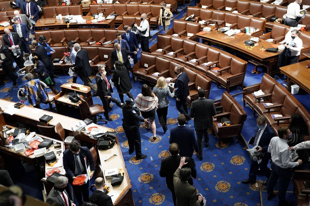 Members of Congress evacuate the House Chamber as protesters attempt to enter during a joint session of Congress in Washington on Jan 6, 2021.
