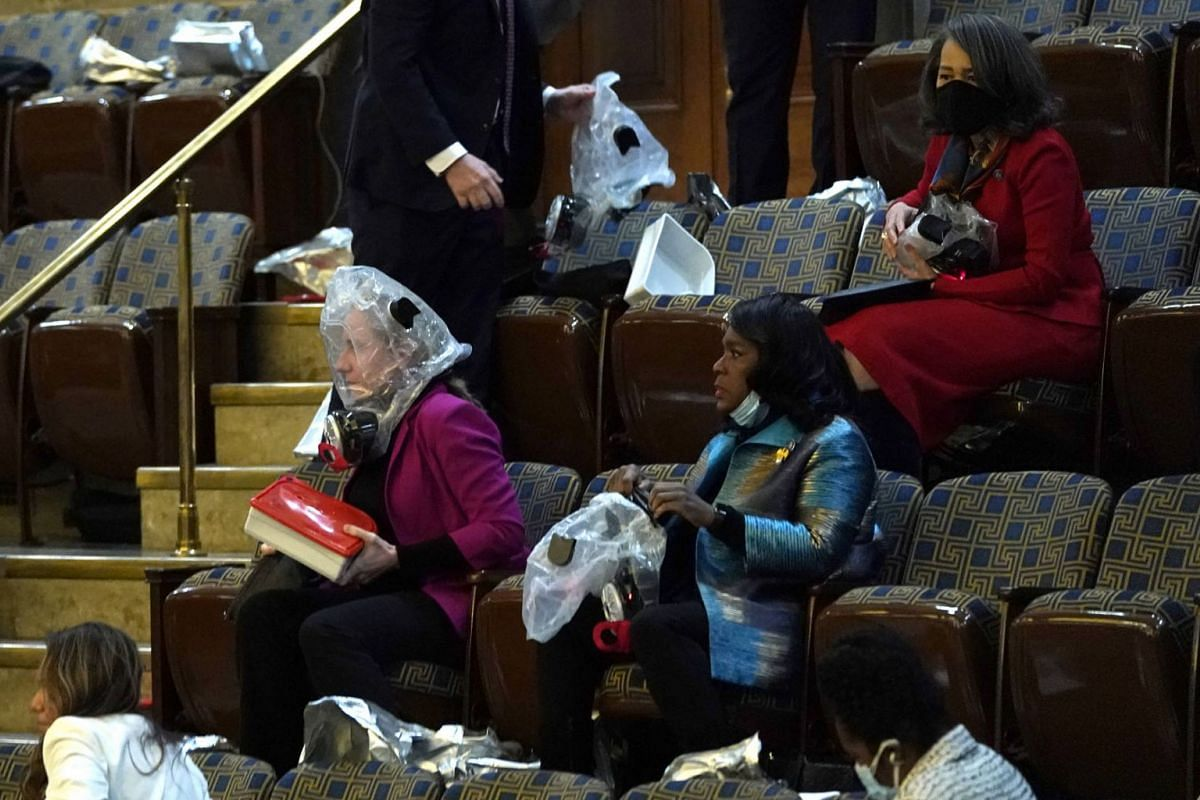 People wear plastic respirators as they are evacuated from the House Chamber as protesters attempt to enter the chamber during a joint session of Congress on Jan 6, 2021 in Washington, DC.