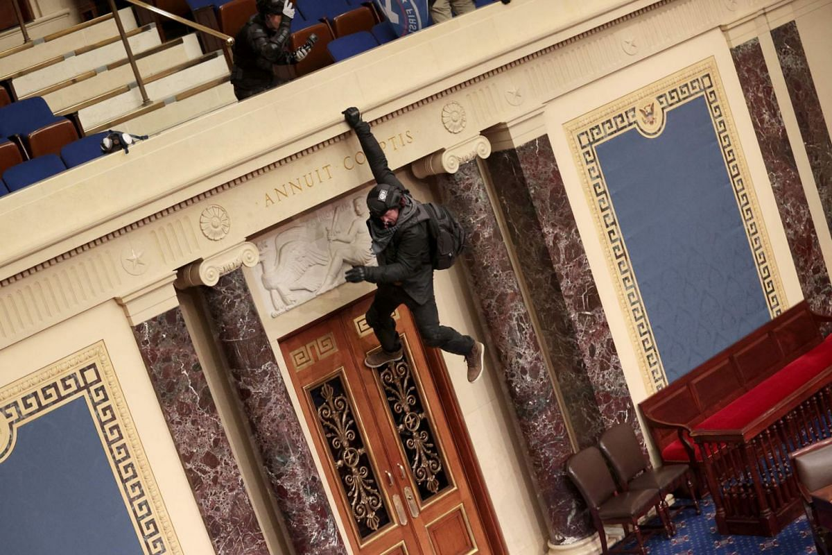 A protester is seen hanging from the balcony in the Senate Chamber on Jan 6, 2021 in Washington, DC.
