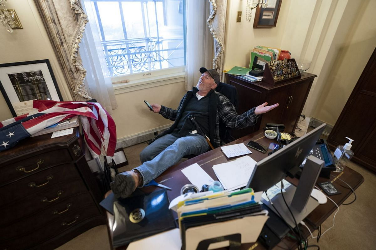 A supporter of US President Donald J. Trump sits on the desk of US House Speaker Nancy Pelosi, after supporters of US President Donald J. Trump breached the US Capitol security in Washington, DC, USA, Jan 6, 2021.