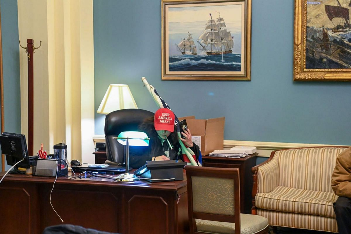 A supporter of US President Donald Trump sits at a desk after invading the Capitol Building on Jan 6, 2021, in Washington, DC.