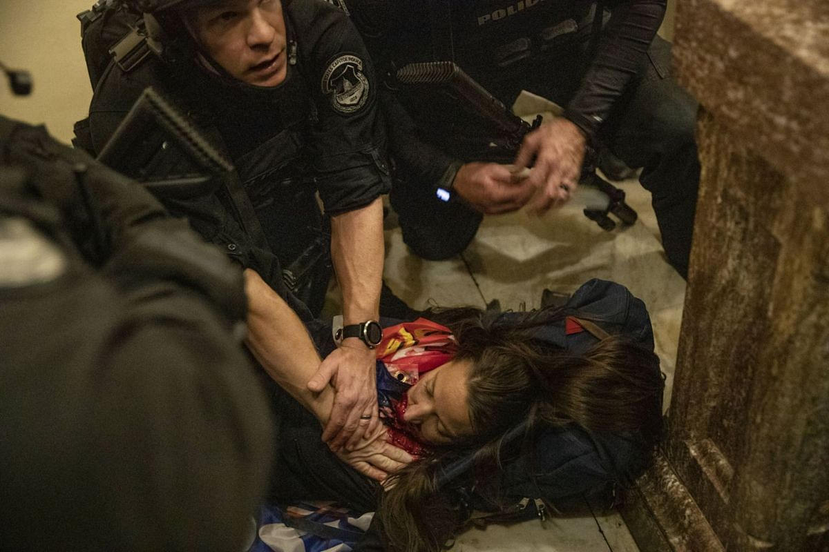 A person lies on the ground after being shot during a protest at the US Capitol in Washington, DC, US, on Wednesday, Jan 6, 2021.