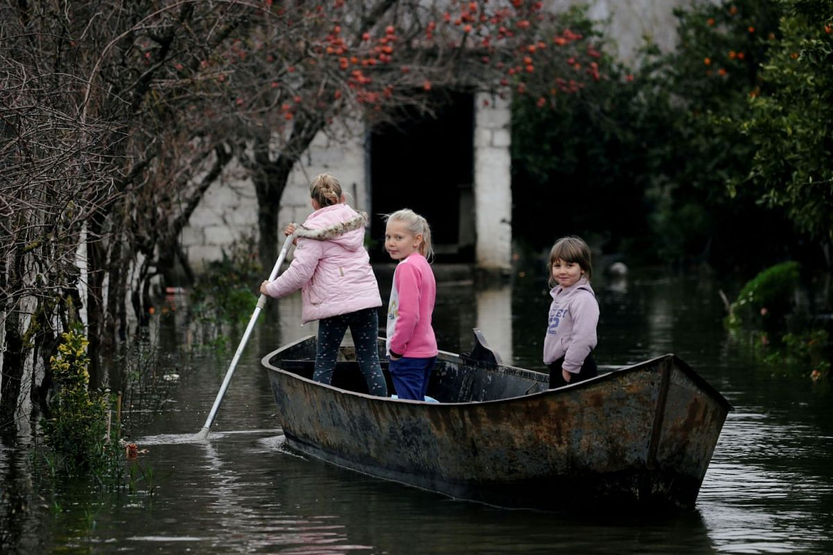 Children use a boat at a flooded area in Obot village, near Shkodra, Albania, Jan, 12, 2021.