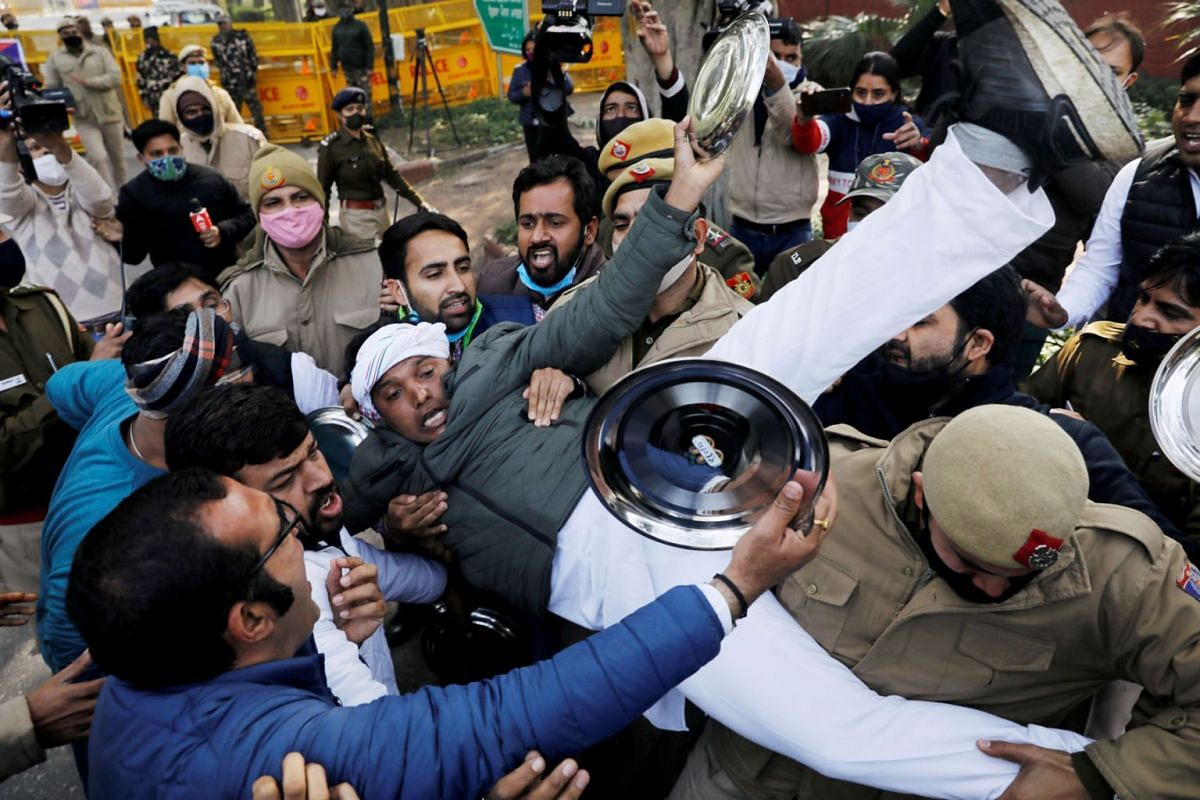 Police officers detain an activist of the youth wing of India's main opposition Congress party during a protest against new farm laws in New Delhi, India, Jan 12, 2021.
