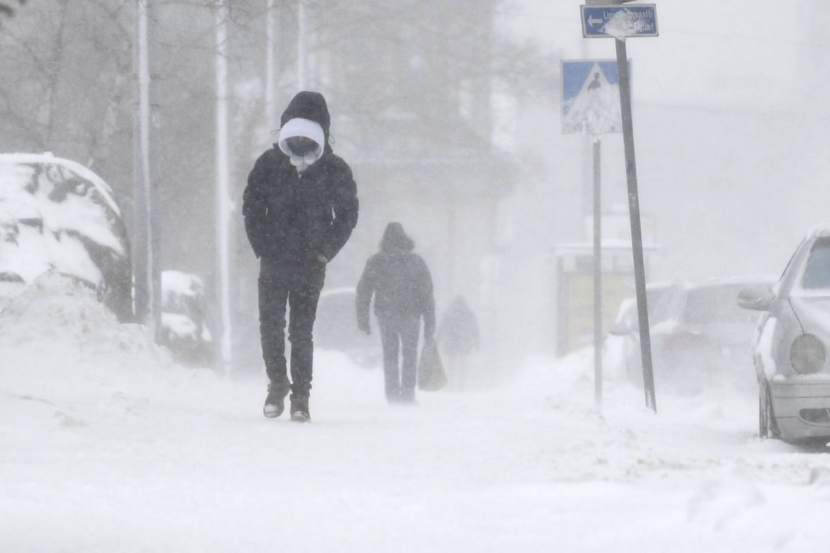 Pedestrians make their way through a thick layer of snow covering the streets of Helsinki, Finland, on Jan 12, 2021.