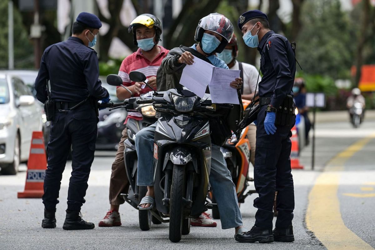 Police check documents of motorists at a checkpoint in Kuala Lumpur on Jan 13, 2021, a day after Malaysian authorities imposed tighter restrictions on movement to try to halt the spread of the Covid-19 coronavirus.