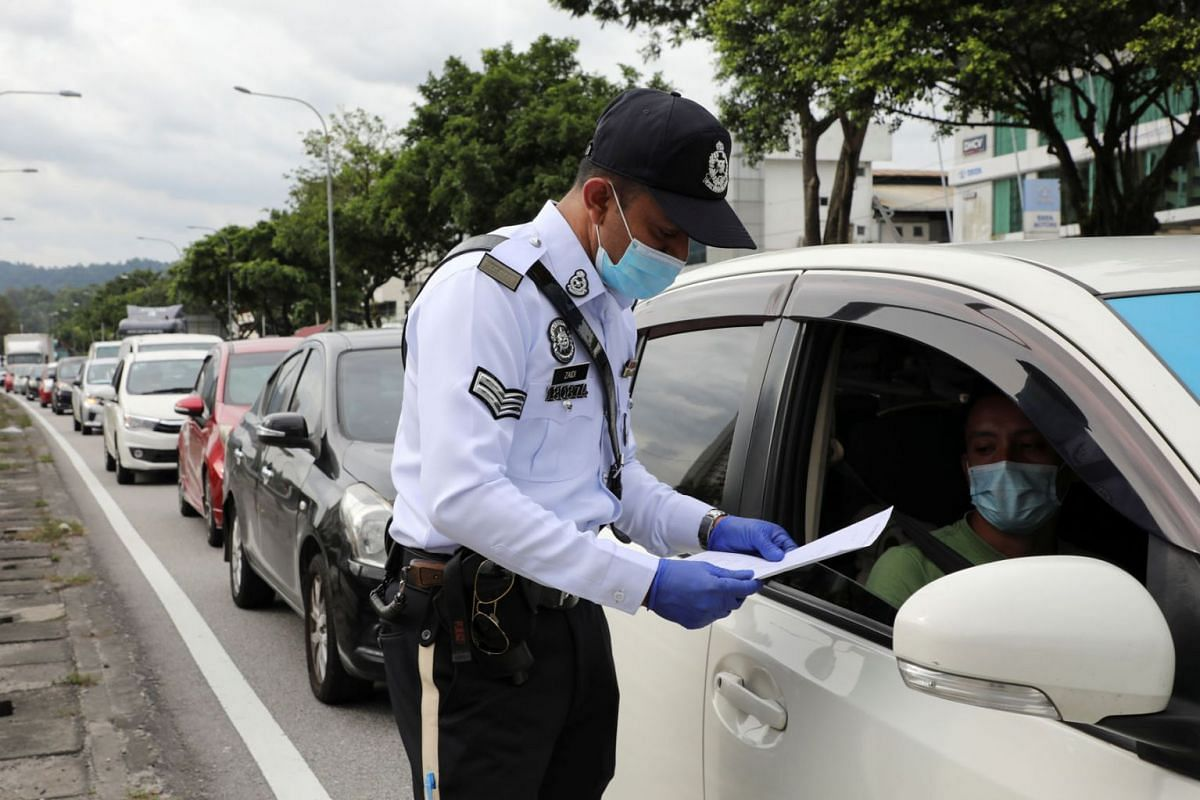 A police officer checks the documents of a driver at a roadblock during a lockdown amid the coronavirus disease (COVID-19) outbreak, in Kuala Lumpur, Malaysia, Jan 13, 2021.