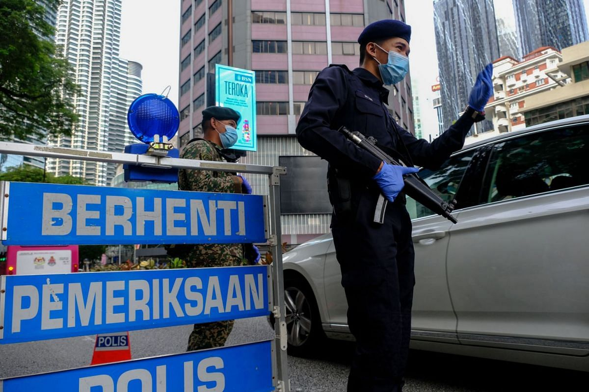 A police officer and a member of the Malaysian Army wear protective masks at a checkpoint during a nationwide state of emergency in Kuala Lumpur, Malaysia, on Jan, 13, 2021.