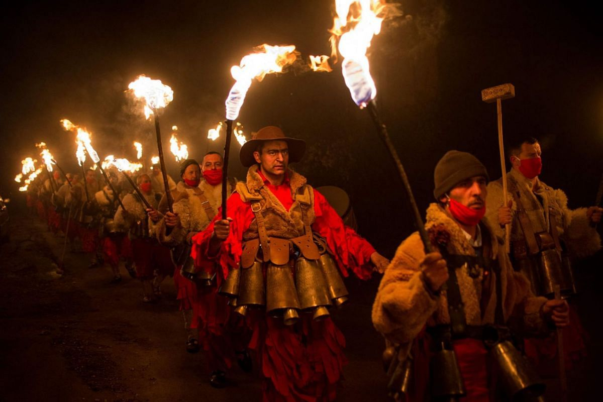 Bulgarian dancers wearing costumes perform a ritual dance with flaming torches during the Kukeri Carnival in the village of Dolna Sekirna, western Bulgaria, on Jan 13, 2021.
