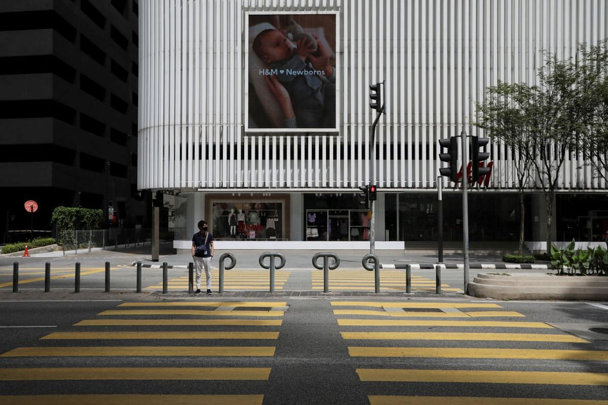 A man waits to cross a deserted street outside a shopping mall, during a lockdown due to the coronavirus disease outbreak, in Kuala Lumpur, Malaysia Jan 13, 2021.