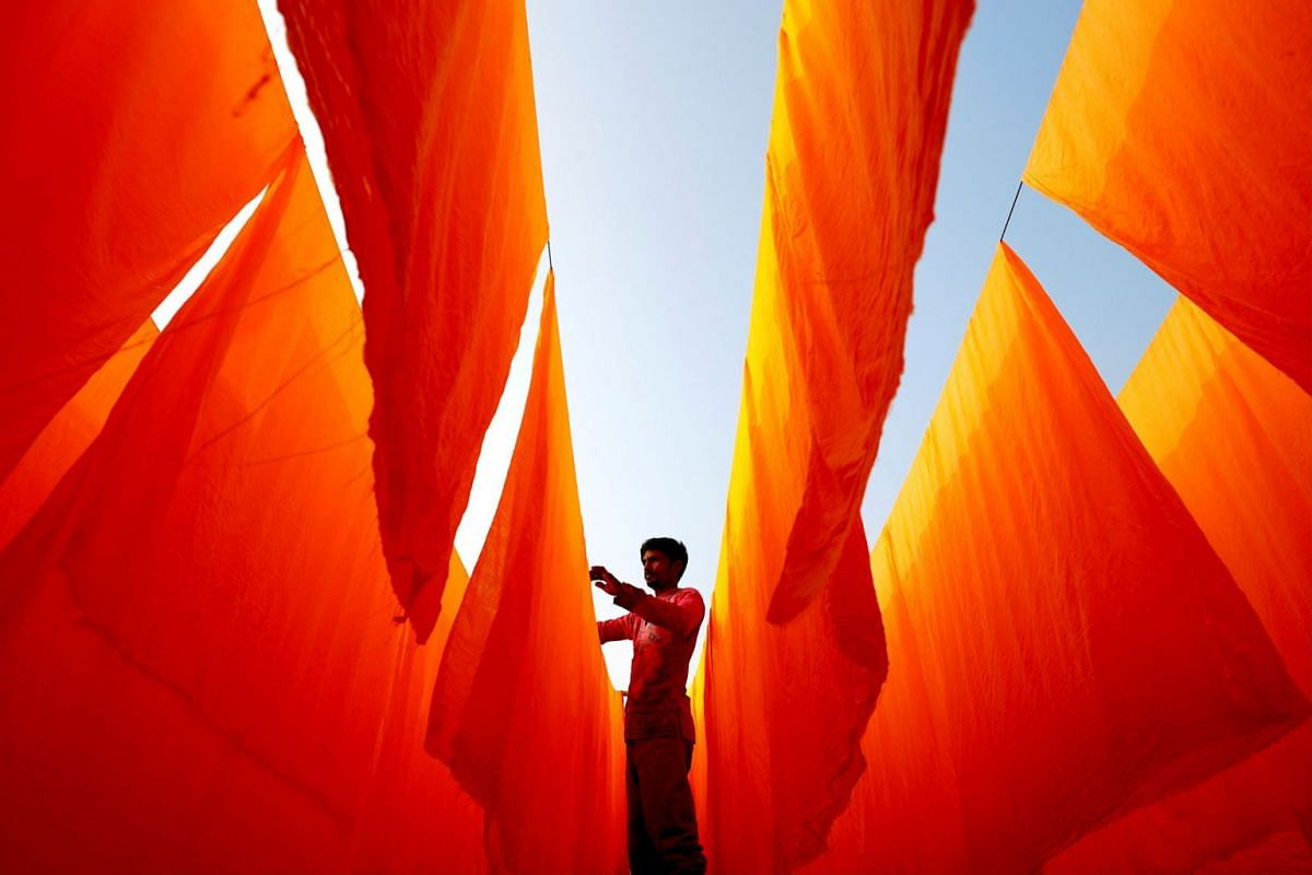 A worker dries fabrics after applying color at a dye factory in Narayanganj, Bangladesh, Jan 13, 2021.