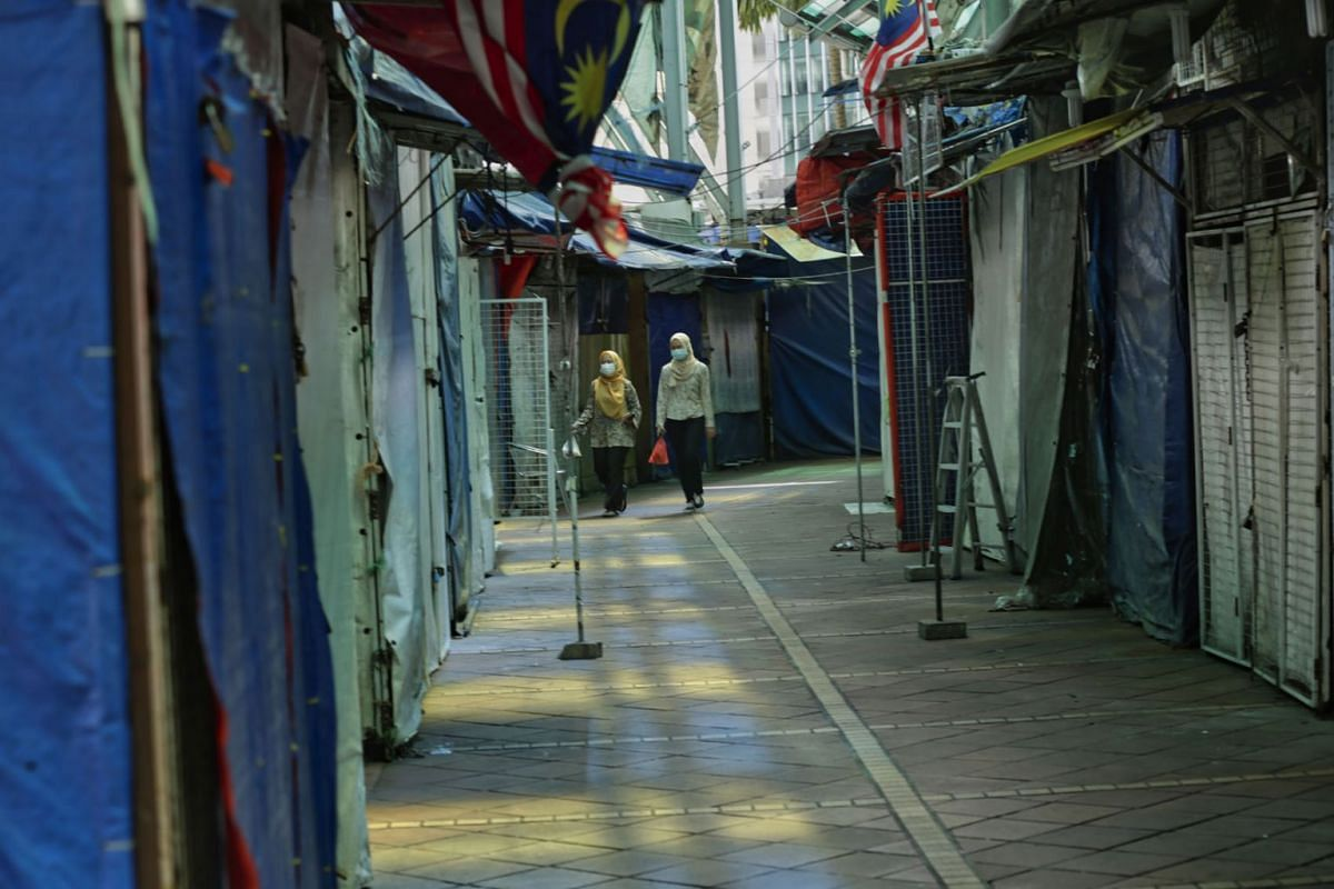 A woman walks past a closed shop at a bazaar area on day one of the implementation of Movement Control Order (MCO) 2.0, in Kuala Lumpur, Malaysia, on Jan 13, 2021.