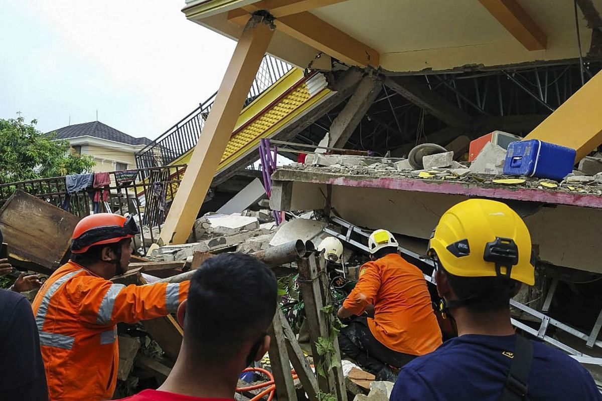 A handout picture made available by the Indonesian National Search and Rescue Agency (BASARNAS) shows rescuers searching for victims under the rubble of a collapsed building following a 6.2 magnitude earthquake in Mamuju, West Sulawesi, Indonesia, Ja