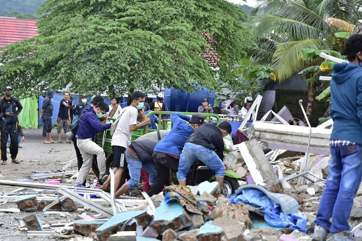 Rescuers search for survivors at a collapsed building in Mamuju city on Jan 15, 2021, after a 6.2-magnitude earthquake rocked Indonesia's Sulawesi island.