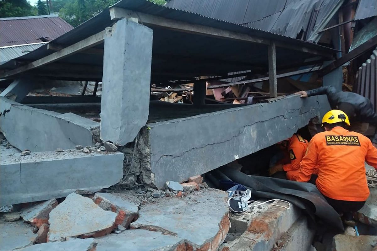 This handout photo taken and released on January 15, 2021 by Indonesia's National Disaster Agency (BASARNAS) shows rescuers looking for survivors trapped in a collapsed building in Mamuju, after a 6.2-magnitude earthquake rocked Sulawesi island.