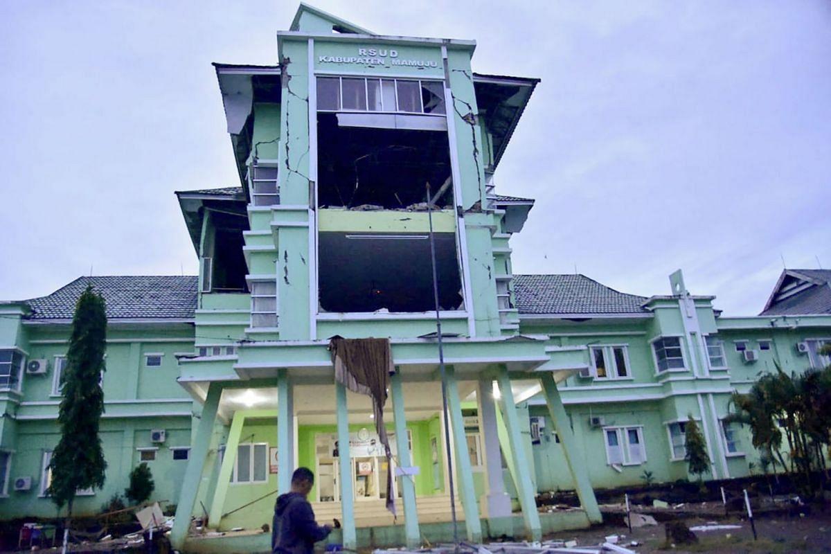 A man walks by a damaged hospital in Mamuju city on Jan 15, 2021, after a 6.2-magnitude earthquake rocked Indonesia's Sulawesi island.