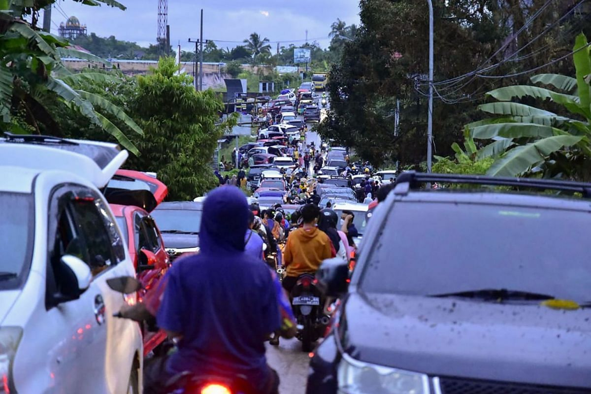 Residents crowd a road as they attempt to leave Mamuju on Jan 15, 2021, after a 6.2-magnitude earthquake rocked Indonesia's Sulawesi island.