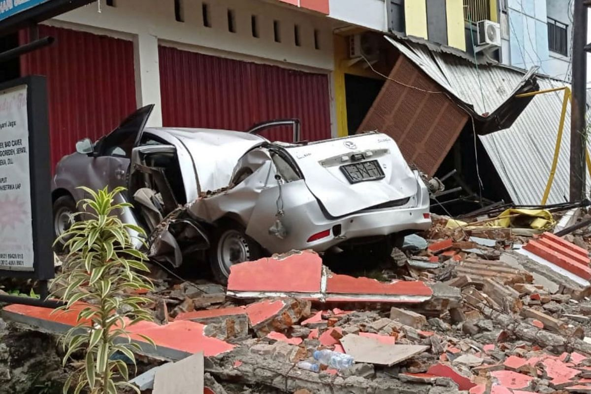 A damaged car and buildings are seen following an earthquake in Mamuju, West Sulawesi province, Indonesia, Jan 15, 2021 in this photo taken by Antara Foto.