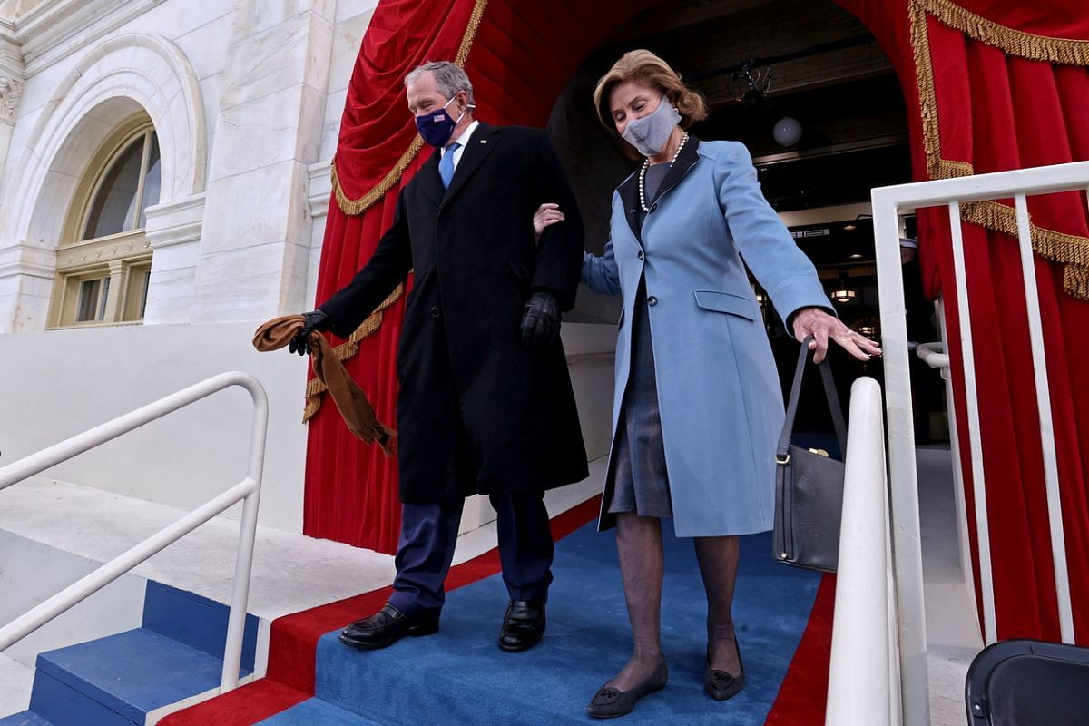 Former US President George W. Bush and his wife Laura Bush arrive for the inauguration.